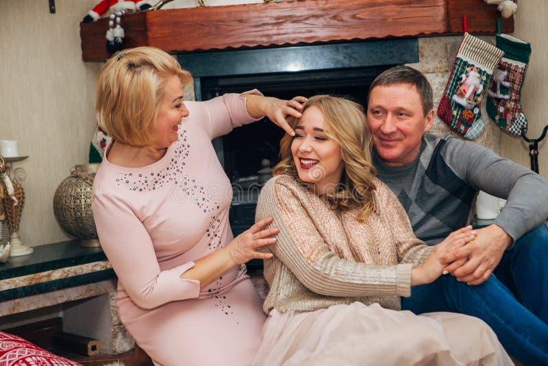 Föräldrar samman med tonårigt posera för dotter för kameran fotografering för bildbyråer