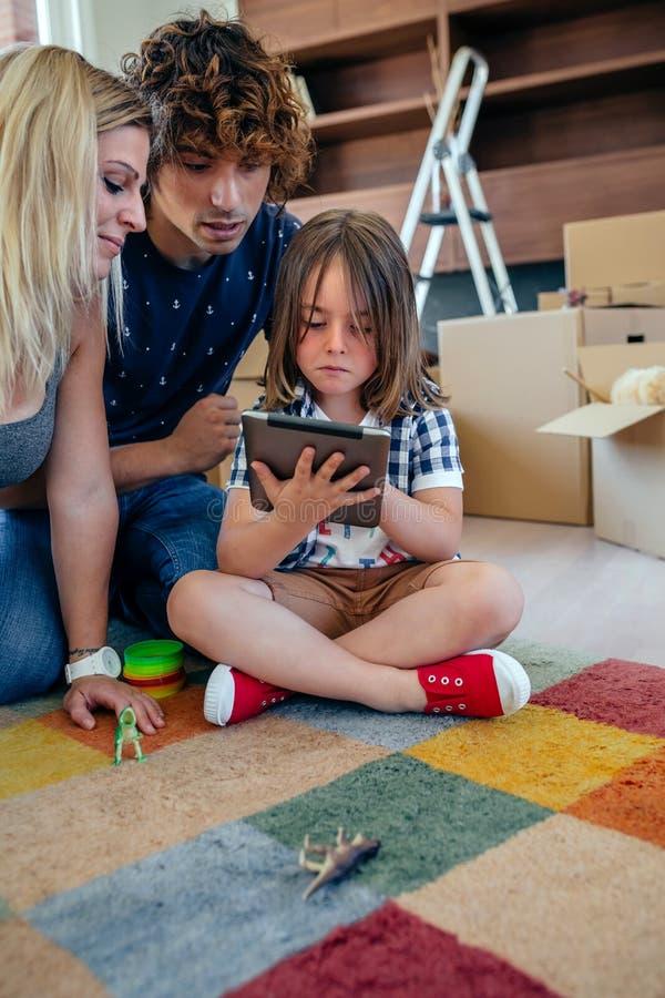 Föräldrar som övervakar deras lilla son spela minnestavlan royaltyfria bilder