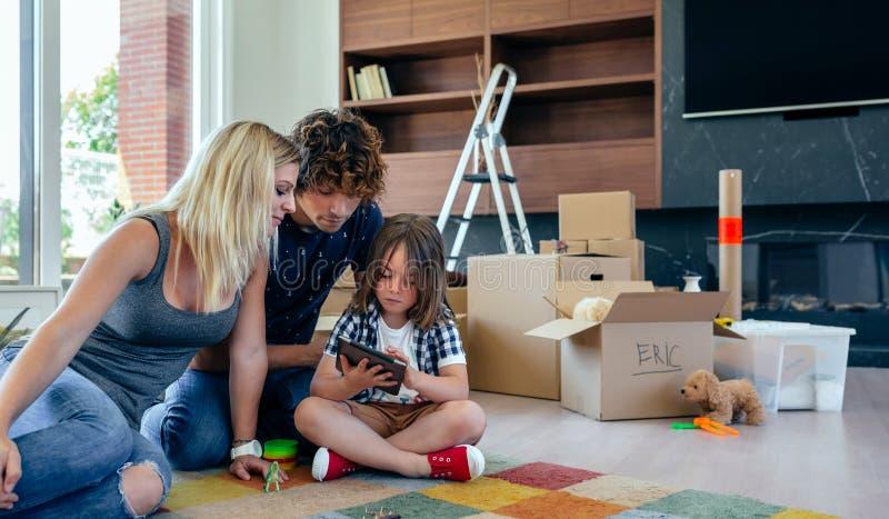 Föräldrar som övervakar deras lilla son spela minnestavlan royaltyfri bild