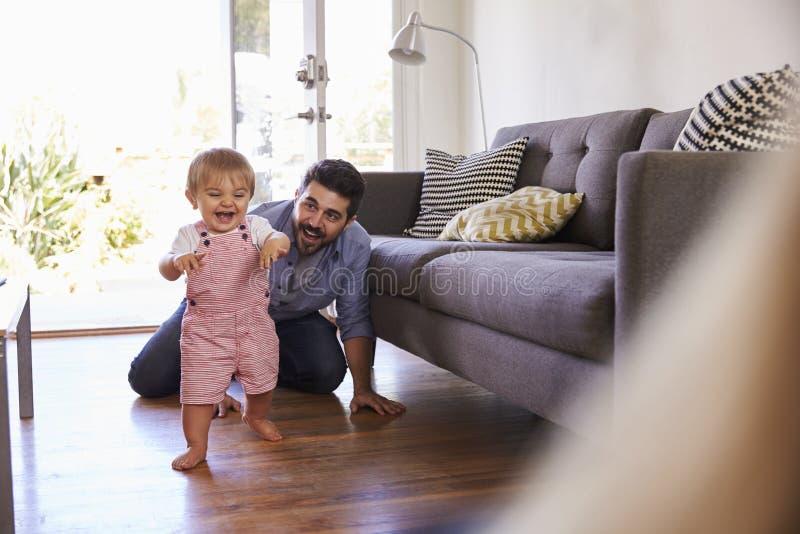 Föräldrar som att hålla ögonen på behandla som ett barn dottern, tar första steg hemma royaltyfria bilder