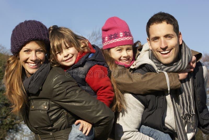 Föräldrar som ger ridturer på axlarna till barn på vinter, går arkivfoto