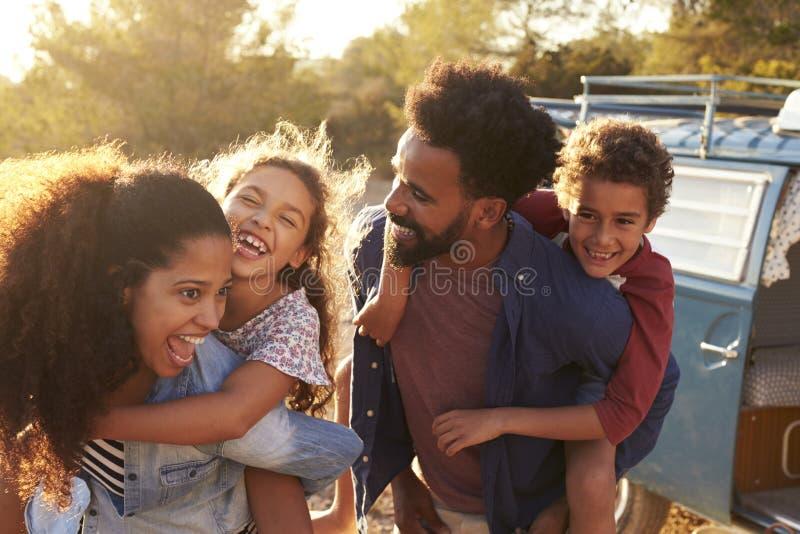 Föräldrar som ger upp deras ungar ridturer på axlarna, midja royaltyfri fotografi