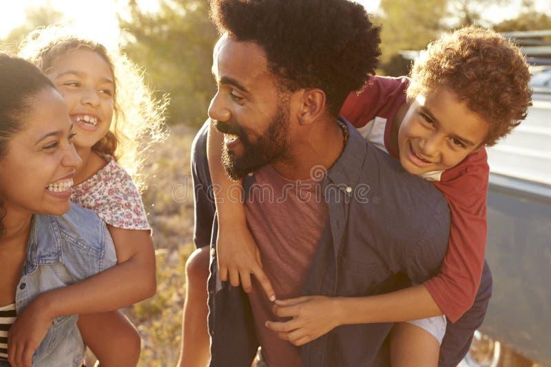 Föräldrar som ger upp deras ungar ridturer på axlarna, midja, tätt upp royaltyfria foton