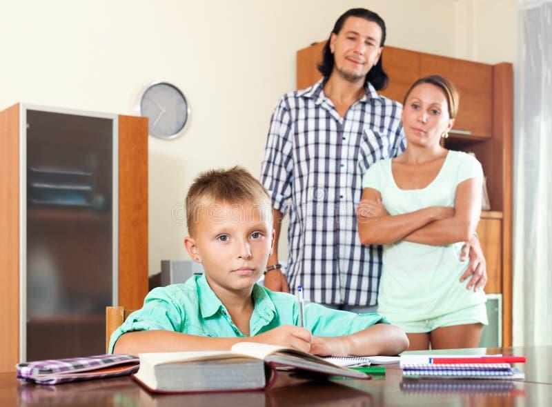 Föräldrar som håller ögonen på deras son göra läxa arkivfoto
