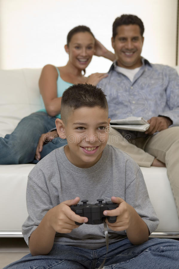 Föräldrar som håller ögonen på sonen att spela videospel i främre sikt för vardagsrum royaltyfri fotografi