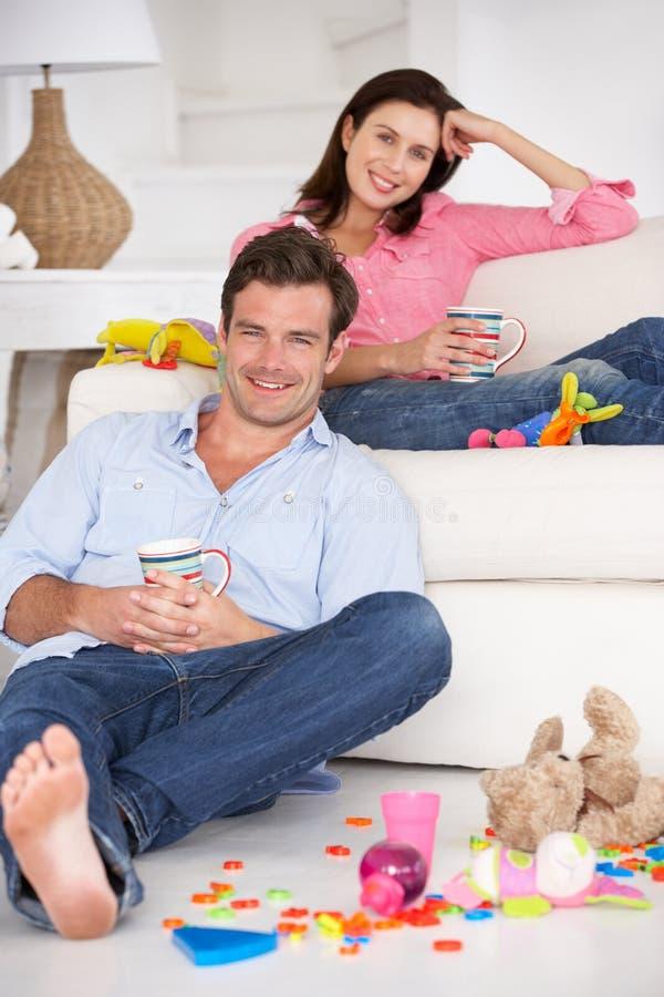 Föräldrar som hemma tycker om en rest royaltyfria bilder