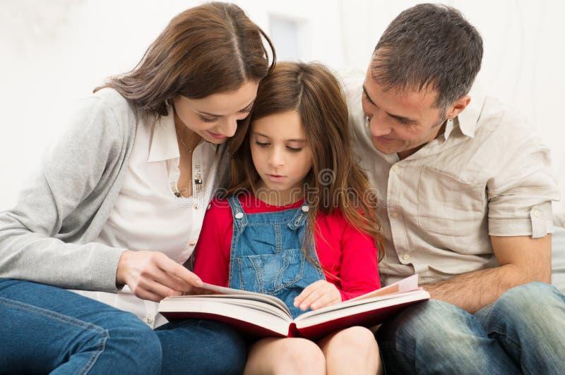 Föräldrar som hjälper dottern i studier fotografering för bildbyråer