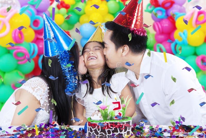 Föräldrar som kysser deras barn i födelsedagparti arkivfoton