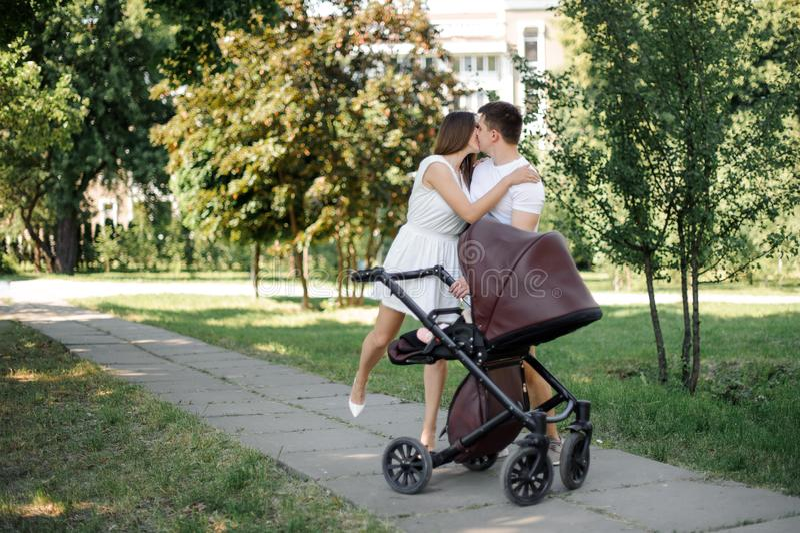Föräldrar som kysser nära deras dotter i den babby vagnen arkivfoton