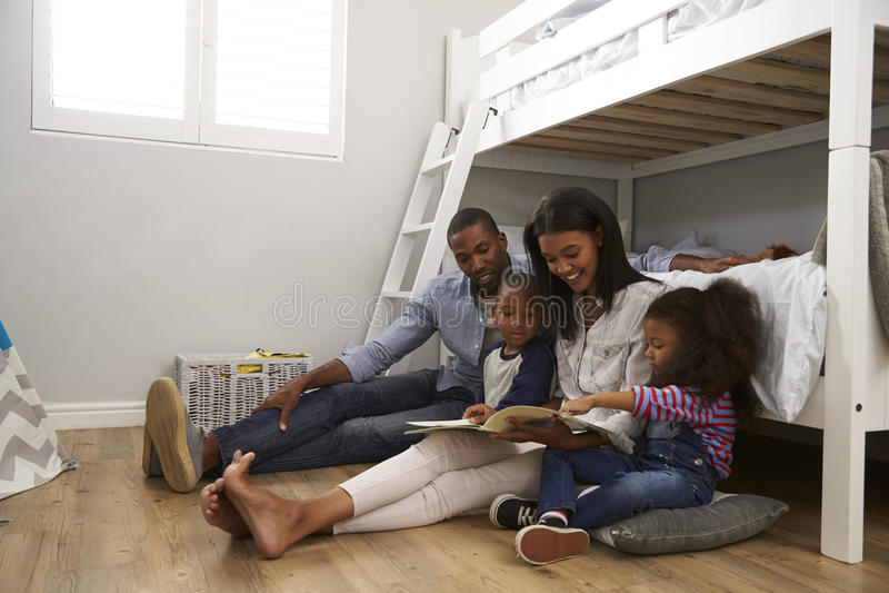 Föräldrar som läser berättelse till barn i deras sovrum royaltyfria bilder