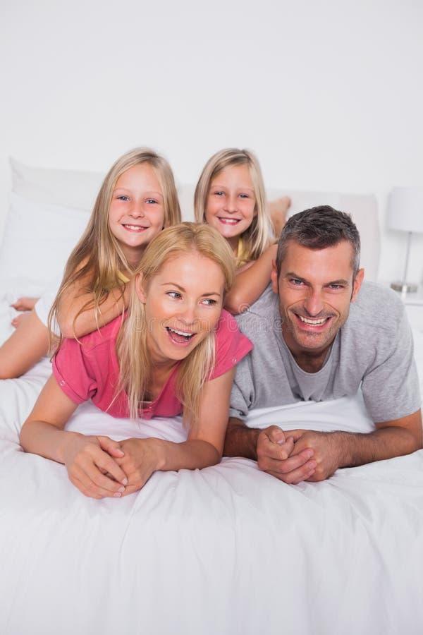 Föräldrar som ligger i säng med deras, kopplar samman royaltyfri foto