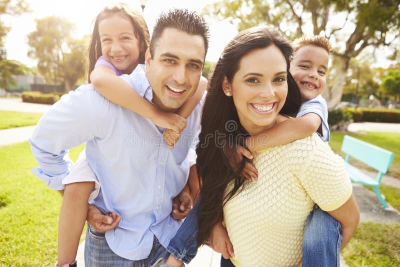 Föräldrar som på ryggen ger ritt för barn i trädgård royaltyfria foton