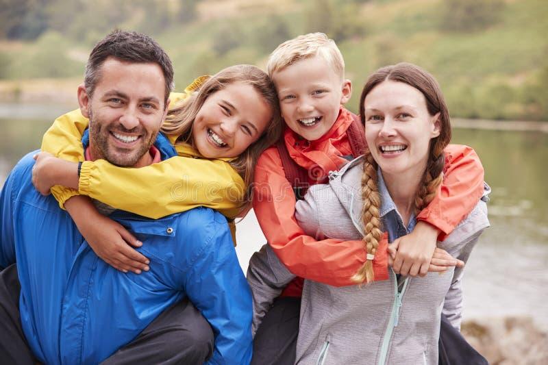 Föräldrar som piggybacking deras barn och skrattar till kameran i bygden, slut upp, sjöområde, UK royaltyfri bild