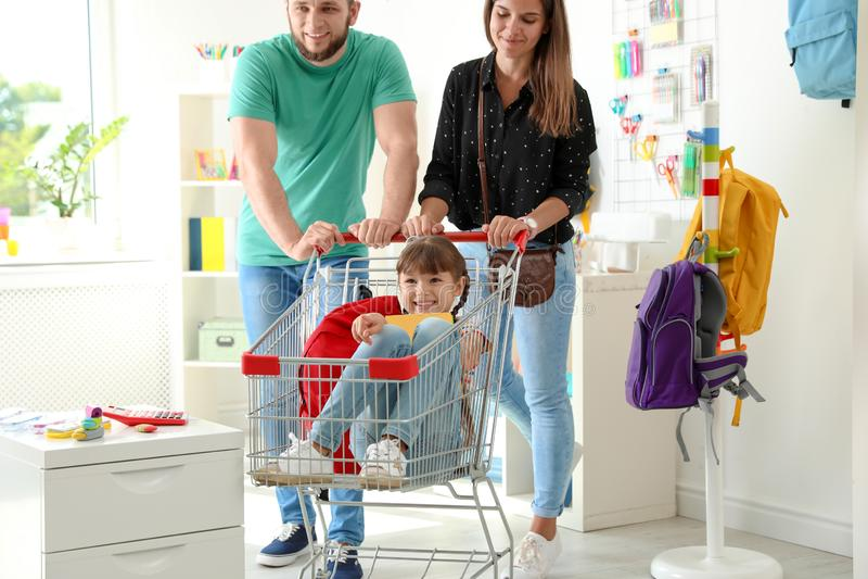 Föräldrar som rider deras barn i shoppingspårvagn arkivbild