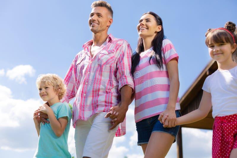 Föräldrar som rymmer deras händer, medan gå med barn arkivbilder