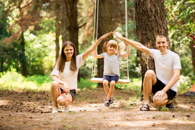 Föräldrar som skjuter barn på gunga i trädgård Familj med barn som gör för evigt för skydd för armtaklöfte arkivfoton