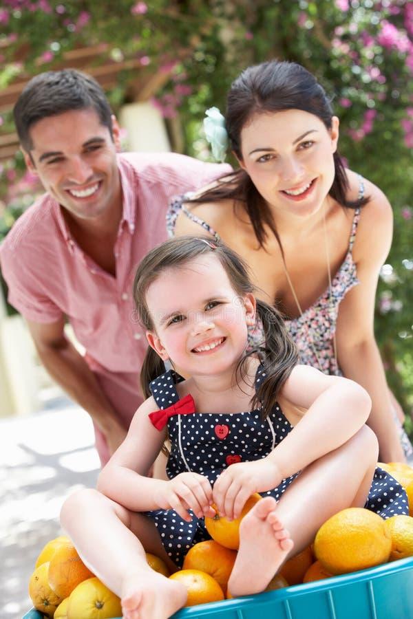 Föräldrar som skjuter dottern i skottkärra royaltyfria foton