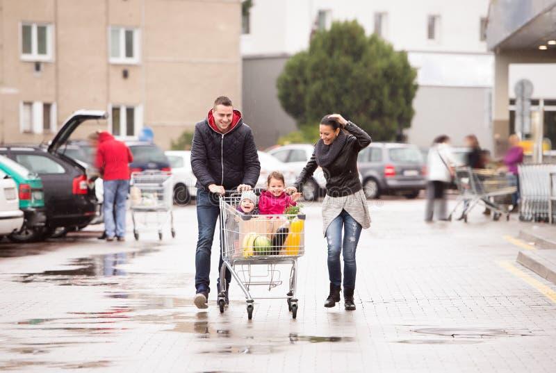 Föräldrar som skjuter shoppingvagnen med livsmedel och deras döttrar arkivbilder