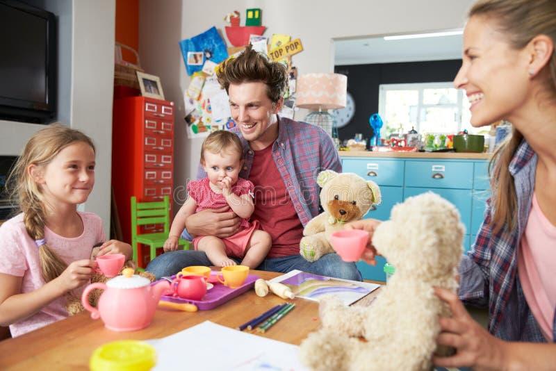 Föräldrar som spelar leken med barn och leksaker i sovrum fotografering för bildbyråer