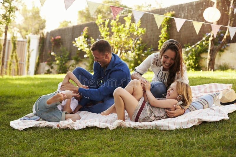 Föräldrar som spelar leken med barn på filten i trädgård arkivfoton