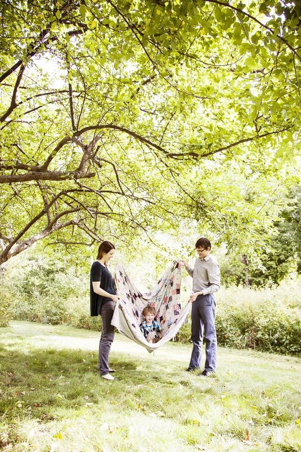 Föräldrar som spelar med barnet i filt royaltyfria bilder