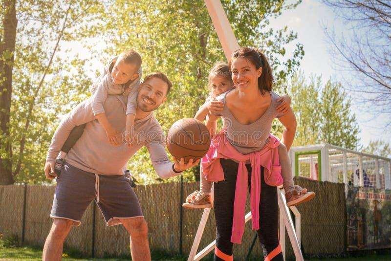 Föräldrar som spelar med deras barn i parkera med korgen, klumpa ihop sig royaltyfri bild