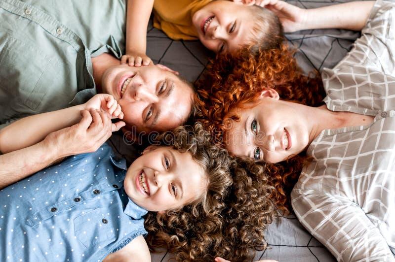 F?r?ldrar som spelar med deras tv? lilla ungar p? s?ng royaltyfria foton