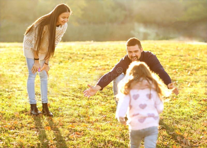 Föräldrar som spelar med dottern parkerar in, på solnedgången royaltyfria bilder