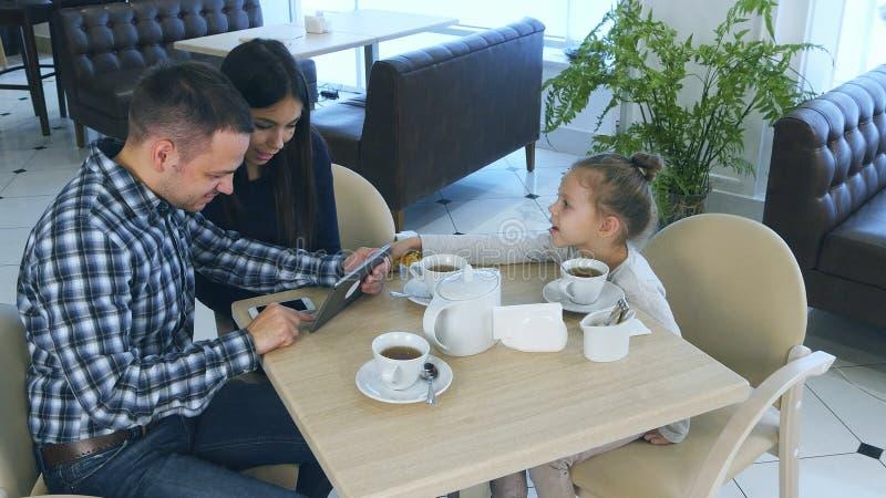 Föräldrar som spenderar tid som ser minnestavlan, medan deras dotter önskar att tilldra deras uppmärksamhet i kafé royaltyfria foton