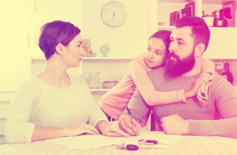 Föräldrar som undertecknar skilsmässalegitimationshandlingar royaltyfri foto