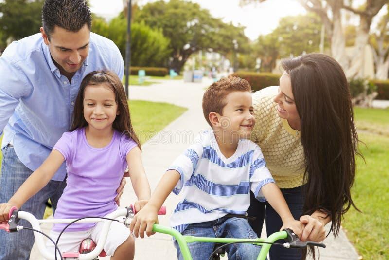 Föräldrar som undervisar barn att rida cyklar parkerar in royaltyfri foto