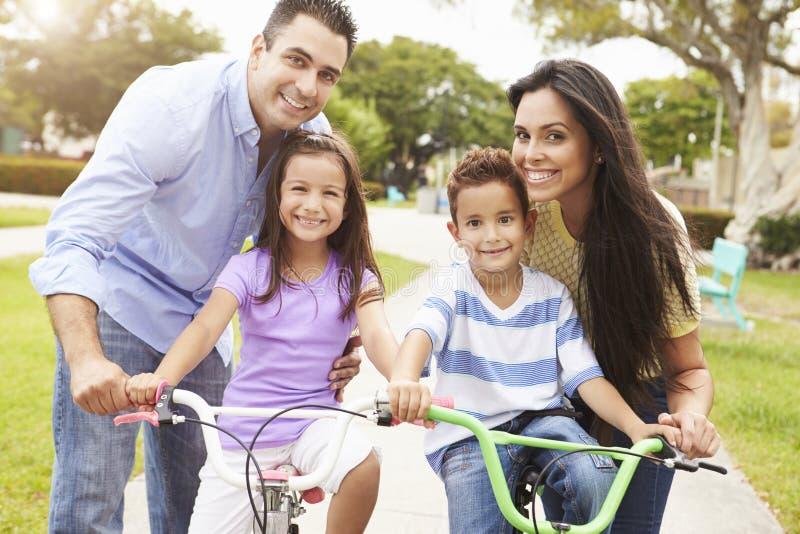 Föräldrar som undervisar barn att rida cyklar parkerar in royaltyfri fotografi