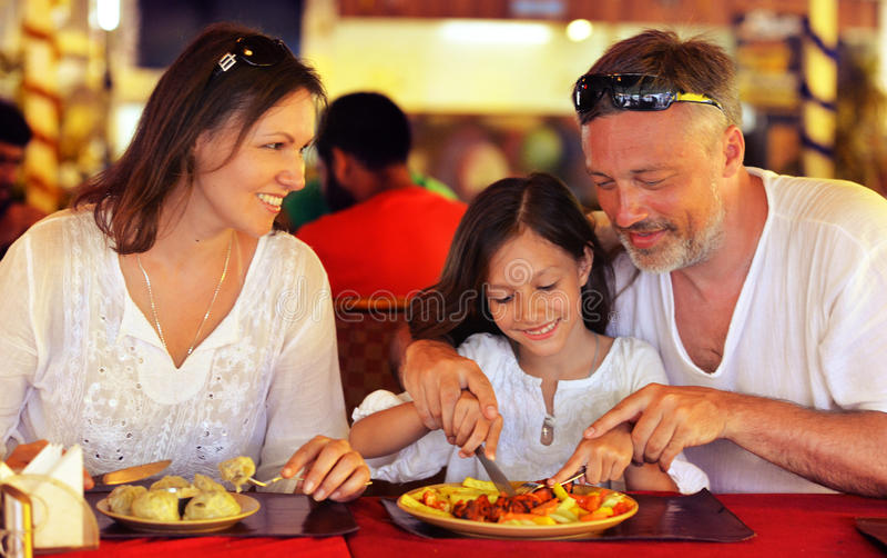 Föräldrar som undervisar dottern att använda kniven arkivbild