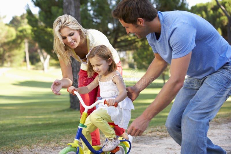 Föräldrar som undervisar dottern att rida cykeln fotografering för bildbyråer