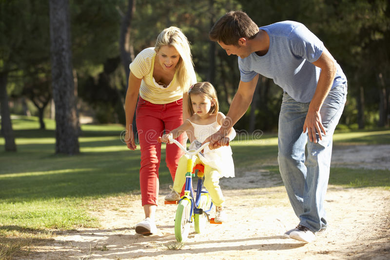 Föräldrar som undervisar dottern att rida cykeln royaltyfri foto