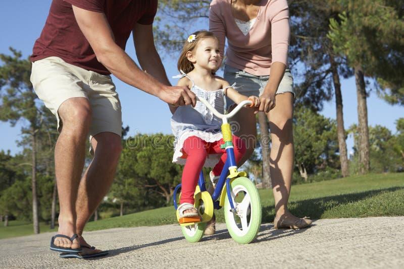 Föräldrar som undervisar dottern att rida cykeln parkerar in royaltyfria foton