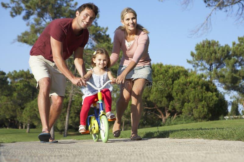 Föräldrar som undervisar dottern att rida cykeln parkerar in royaltyfri fotografi