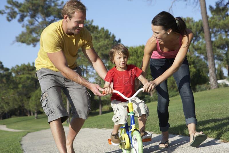 Föräldrar som undervisar sonen att rida cykeln parkerar in arkivfoton