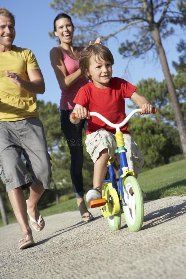 Föräldrar som undervisar sonen att rida cykeln parkerar in arkivbilder