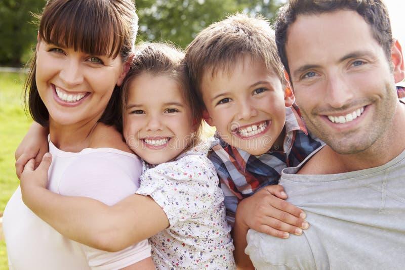 Föräldrar som utomhus ger barn ridturer på axlarna arkivfoton