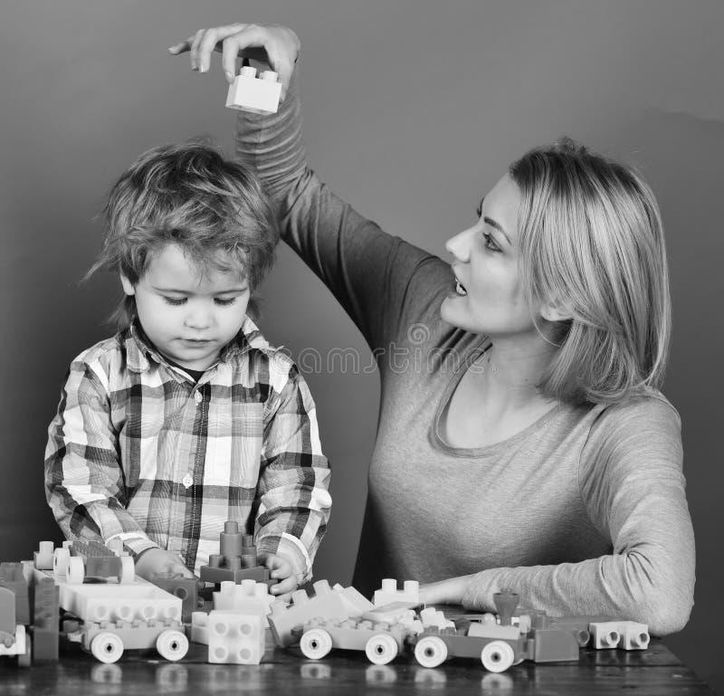 Föräldraskap- och lekbegrepp Kvinna- och pojkelek på röd bakgrund royaltyfria bilder