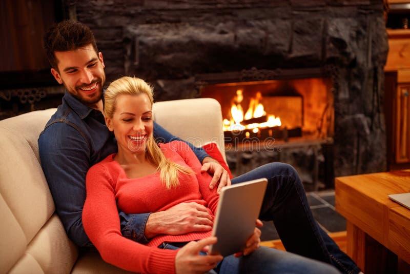 Förälskad användande minnestavla för unga lyckliga par tillsammans royaltyfria foton