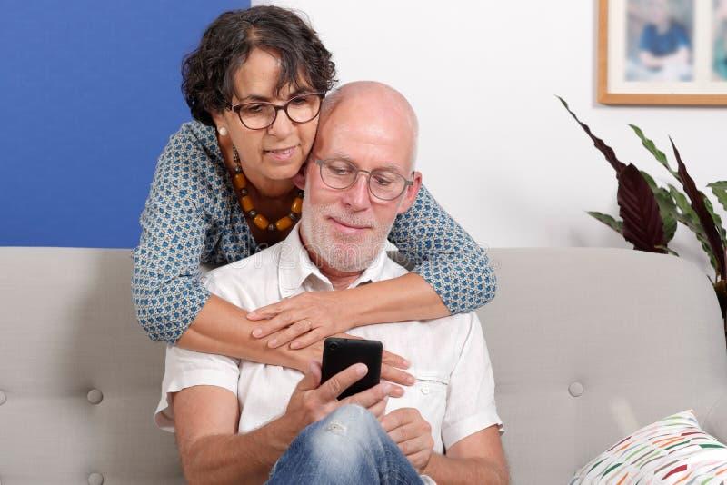 Förälskad användande smartphone för lyckliga höga par, i deras hem arkivfoton