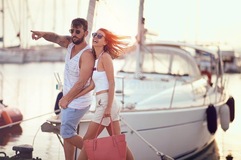 Förälskad hållande hand för par som tycker om i romantiker som går på skeppsdockan på solnedgången fotografering för bildbyråer