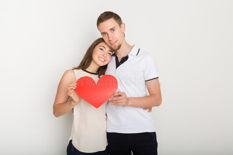 Förälskad hållande röd pappers- hjärta för unga lyckliga par royaltyfri bild