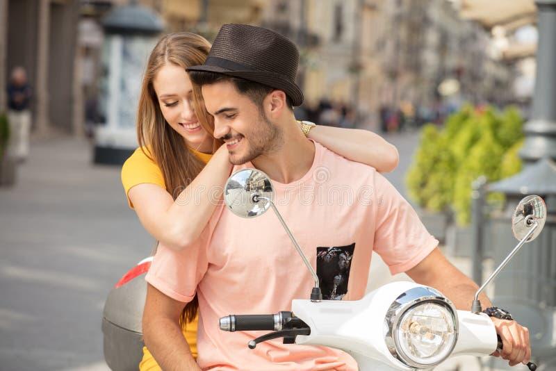 Förälskad ridning för par på en sparkcykel arkivfoto