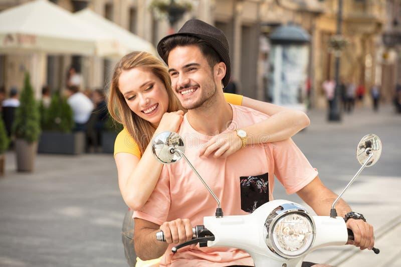 Förälskad ridning för par på en sparkcykel arkivfoton