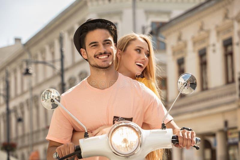 Förälskad ridning för par på en sparkcykel arkivbilder