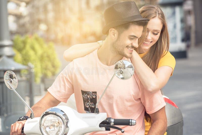 Förälskad ridning för par på en sparkcykel royaltyfri foto