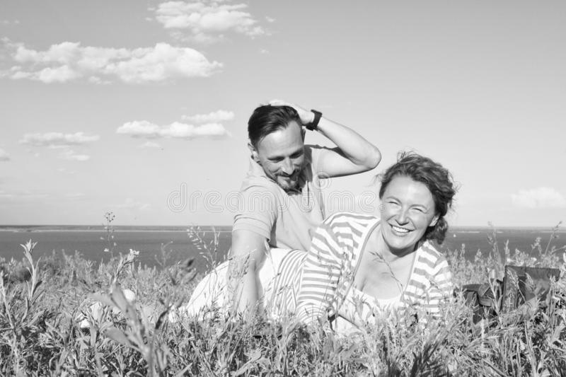 Förälskade attraktiva par ha roligt och tycka om den härliga naturen och de blåa himlarna med moln Le och lycklig kvinna i gräs royaltyfri foto